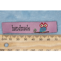 "Tag, pink, black embroidered wording ""handmade "" with colourful bird on branch symbol"