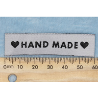 "Tag,white, black embroidered wording ""HAND MADE "" with 2 black heart symbols"