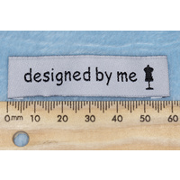 "Tag,white, black embroidered wording ""designed by me "" with dress maker dummy symbol"