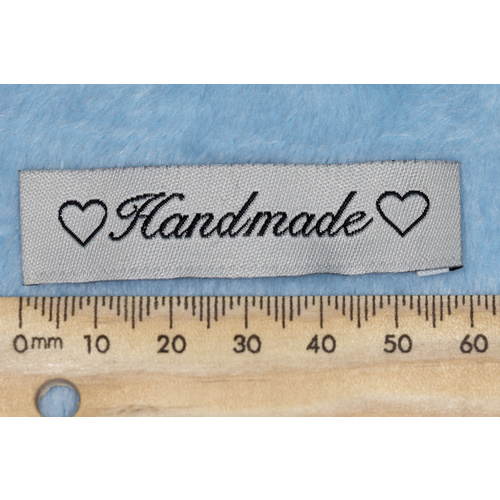 "Tag, cream, black embroidered wording ""Handmade "" with 2 heart symbols"